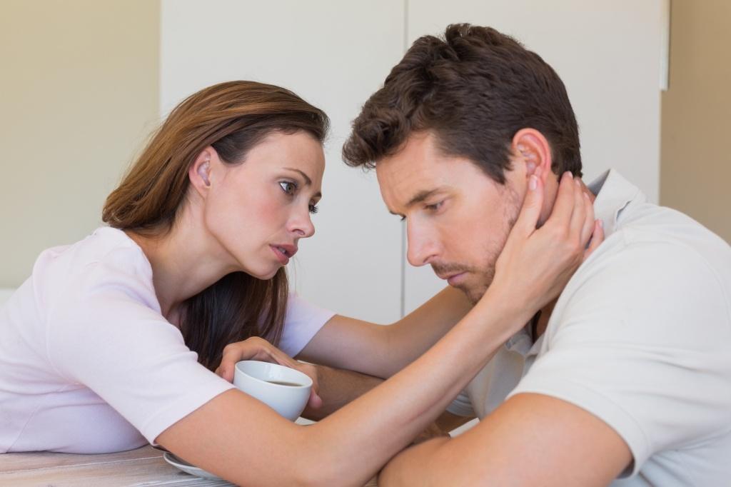 woman consoling a sad man at home